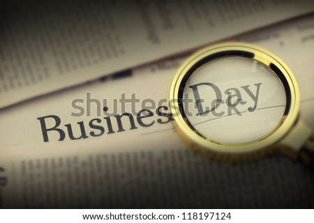Loupe lies on the newspaper with title Business day. Selective lighting on an inscription.A photo close up. Selective focus - stock photo