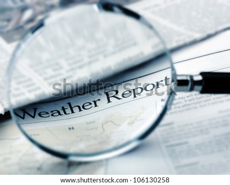Loupe lies on the newspaper with title Weather report.Blue toned. A photo close up. Selective focus - stock photo