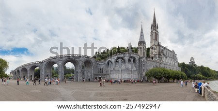 LOURDES, FRANCE - JULY 23, 2014: Tourists and Pilgrims visiting the Sanctuary of Our Lady of Lourdes. Lourdes is able to take in some 5,000,000 pilgrims and tourists every season.