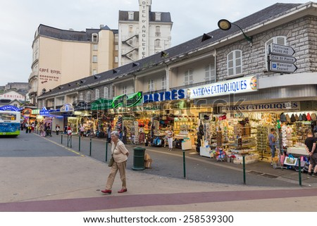 LOURDES, FRANCE - JULY 23, 2014: Typical souvenir shop as found in Lourdes, France. Most of the shopping opportunities in Lourdes are especially conceived for pilgrims. - stock photo