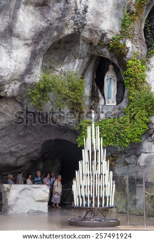 LOURDES - JULY 23, 2014: Candles displayed at the cave at Massabielle in Lourdes, where St. Bernadette Soubirous claimed to have seen the Blessed Virgin Mary. It now is a religious grotto.
