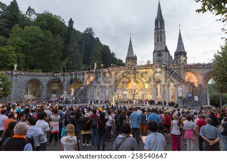 LOURDES - JULY 23, 2014: Pilgrims partaking in La Procession Mariale Aux Flambeaux or the Torchlight Marian Procession in Lourdes. The torchlight procession takes place at the Domain daily at 9.00pm.