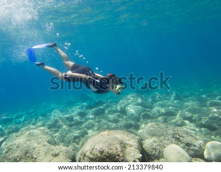 LOUTRA,GREECE-AUGUST 24 2014 :A female snorkeler dives beneath the surface to explore underwater.Snorkeling is an easy sport for all ages to take part in - stock photo