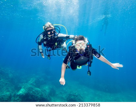 LOUTRA,GREECE-AUGUST 24 2014 :Female Scuba Diver taking part in a training dive with her Instructor.More women are taking up diving with dive schools around the world - stock photo