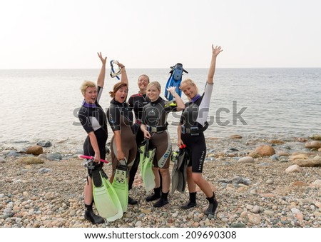 LOUTRA,GREECE - JULY 26 2014 : Female Scuba Divers after a training dive.More women are taking up the adventurous sport  of scuba diving .There are dive schools in most countries around the world. - stock photo