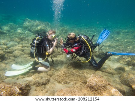 LOUTRA,GREECE - JULY 26 2014 : Female Scuba Divers take part in a traing dive.More women are taking up the adventurous sport  of scuba diving .There are dive schools in most countries around the world - stock photo