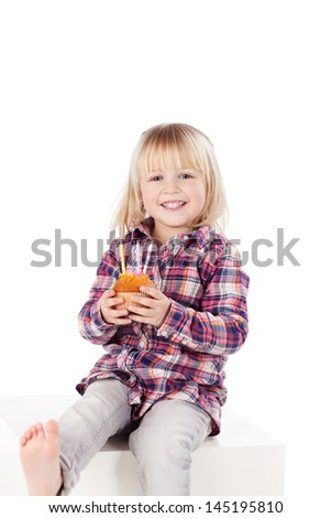 Lovable little blond girl with a birthday cake with four candles held carefully in her hand sitting barefoot on a white cabinet - stock photo
