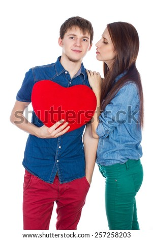 Love a wonderful feeling! Beautiful young happy couple kissing behind a red heart, holding it in hands. Brunettes, girl and boy lovers are isolated on a white background in denim shirt and denim pants