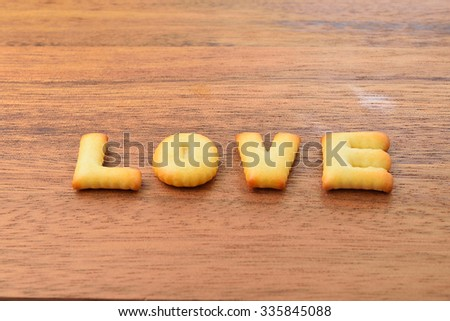love alphabet biscuit on wooden table, stock photo - stock photo