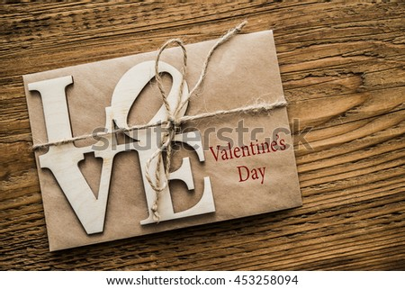 Love alphabet wooden word on brown paper letter. Wooden table background. valentines day - stock photo