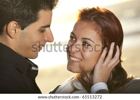 Love and affection between a young couple at the beach in sunny day (selective focus with shallow DOF) - stock photo