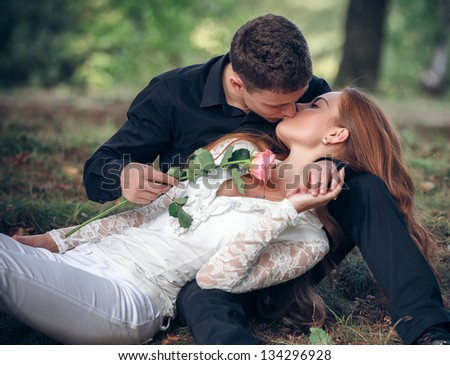Love and affection between a young couple at the park - stock photo