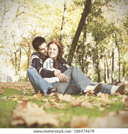 Love and affection between a young couple at the park in autumn season  - stock photo