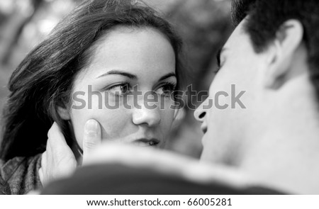 Love and affection between a young couple at the park in autumn season in black and white (selective focus with shallow DOF) - stock photo