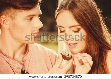 Love and dating. Young handsome man flirting with attractive woman by cupcake cookie. Happy cute lovers on date outdoor. - stock photo