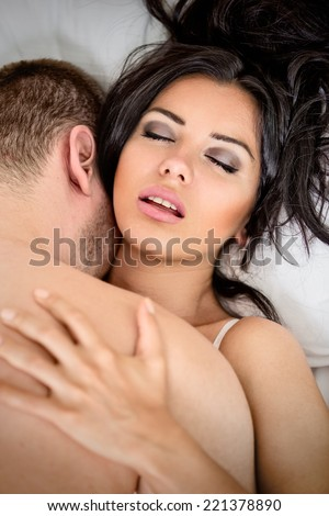 Love and eroticism in the bedroom, couple in bed with sex and affection.  - stock photo