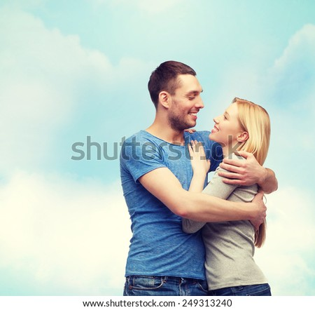 love and family concept - smiling couple hugging and looking at each other - stock photo