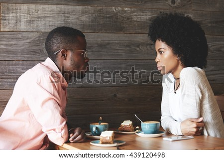Love and friendship concept. Beautiful African young people having a first date at a restaurant, drinking coffee and eating cakes, looking at each other with affection, sitting at the wooden table - stock photo