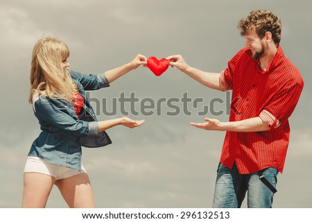 Love and happiness concept. Woman and man young hipster couple in love playing sharing free time having fun holding red heart, outdoor against sky