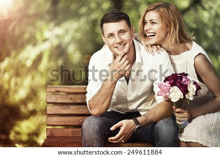 Love and marriage concept. Young attractive cheerful couple in the park and smiling. Woman responded to a marriage proposal. - stock photo
