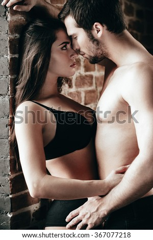 Love and passion. Beautiful young couple bonding to each other and looking eyes to eyes while standing near brick wall