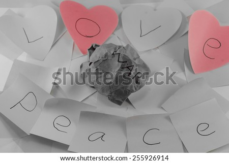 Love and peace written on post it notes with a screwed up peice of paper with war written on it, symbolising, peace and love conquering war, some images with colour removed to certain sections - stock photo