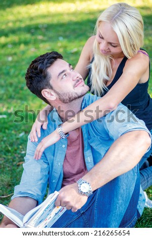 Love and university studies. Couple in love together teach lessons and read a book while sitting on the grass against the building of the university - stock photo