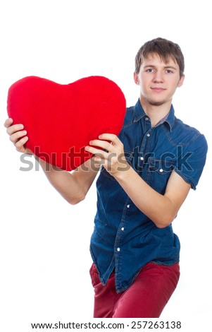 Love and Valentine's Day is a brave and handsome man brunette, standing and holding a red heart, isolated on white background