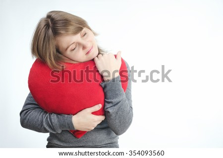 Love and valentines day woman holding heart dreams cute and adorable on a light background - stock photo