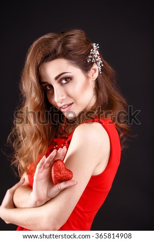 Love and valentines day woman holding heart smiling cute and adorable on black background - stock photo