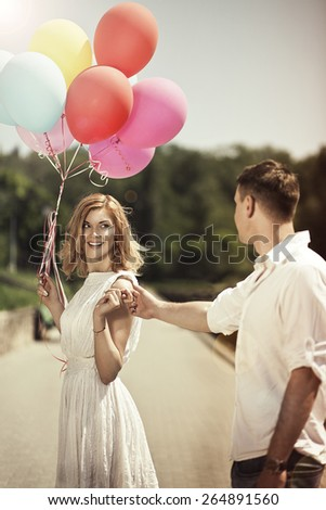 Love and wedding concept. Young attractive happy couple with colorful ballons. Girl fllirting and smiling. Man propose woman. - stock photo