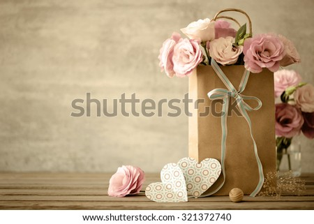 Love background with pink flowers, bow and paper handmade hearts, vintage toned - stock photo