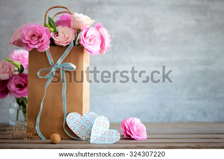 Love background with pink roses flowers, bow and paper handmade hearts - stock photo