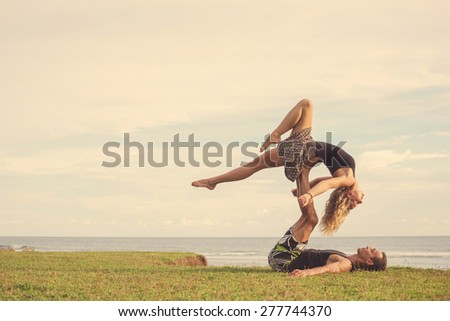 Love beautiful couple on the beach doing dancing fitness yoga exercise together  - stock photo