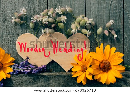 love card / two wooden hearts and wild flowers on the wooden background and inscription wooden wedding / wedding card