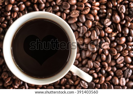 Love coffee cup over coffee beans background with copy space, coffee cup on coffee beans backdrop close up - stock photo