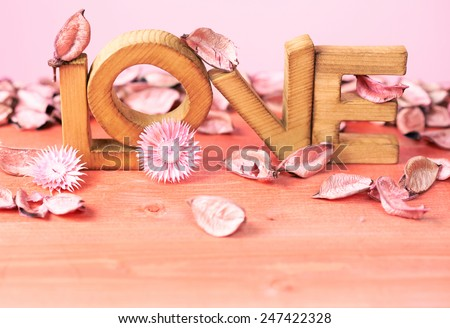Love composition of wooden block letters covered with the dried flower potpourri agains the pink background - stock photo