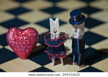 Love concept. Clothespins: romantic couple. Bride and groom. Wedding. Valentines day. Gentleman in black hat, woman in black dress. (Soft focus, vintage paper background, retro style) - stock photo