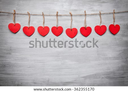 Love concept. Hearts hanging on a string, shot on grey background - stock photo