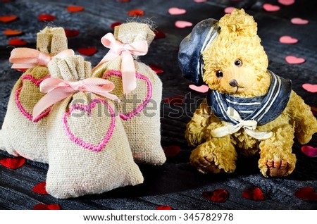 Love concept . Little bear with amorous bags on the black boards with hearts.