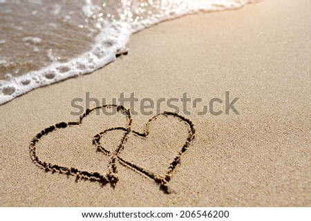 love concept - two hearts drawn on the sand of the beach