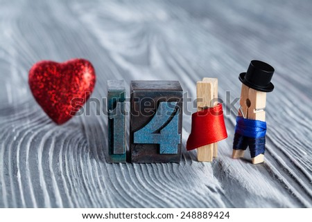 Love concept. Valentines day. 14 february. Romantic couple. Man, woman and read heart. Clothespins. (Soft focus, 14 written with colored vintage letterpress) - stock photo