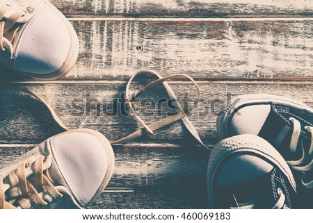 Love concept with sneakers on wooden floor, Valentine's day concept, Heart shape of shoelace on wooden floor