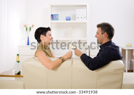 Love couple clinking champagne glasses at home on sofa. Smiling and looking at each other.