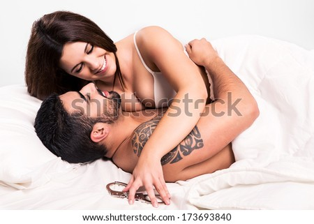 Love couple flirting and hugging in bed