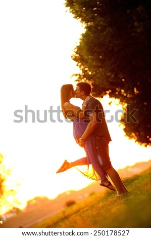 Love couple kissing in the sunset.