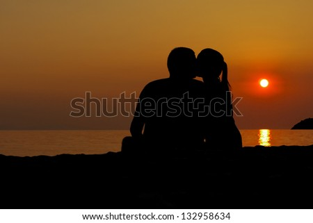 Love couple kissing on the beach as the sun sets, the silhouette - stock photo