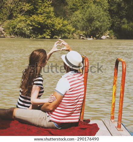 Love Couple Sitting on River Breakwater and Making Heart Shape from Their Hands - stock photo