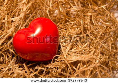 Love cradle with red heart on yellow straw carpet