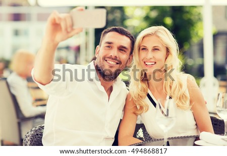 love, date, technology, people and relations concept - smiling happy couple taking selfie with smatphone at city street cafe